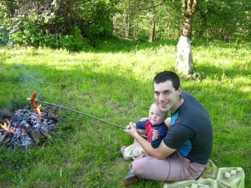 Ondřej pomáhá tatínkovi opékat klobásu